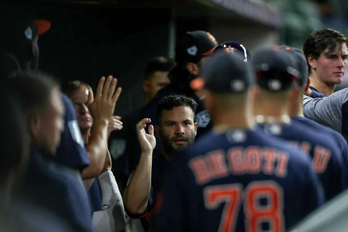 Houston Astros second baseman Jose Altuve (27) is congratulated by teammates after scoring on a single by left fielder Michael Brantley (23) during the third inning of a spring training game at Minute Maid Park on Monday, March 25, 2019, in Houston.