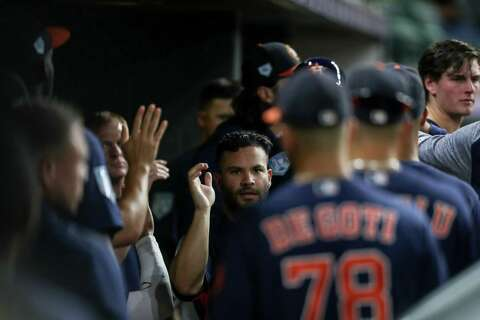 Houston Astros second baseman Jose Altuve (27) is congratulated by teammates after scoring on