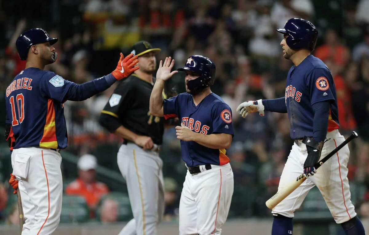Houston Astros second baseman Jose Altuve (27) is congratulated by teammates first baseman Yuli Gurriel (10) and center fielder George Springer (4) after scoring on a single by left fielder Michael Brantley (23) during the third inning of a spring training game at Minute Maid Park on Monday, March 25, 2019, in Houston.