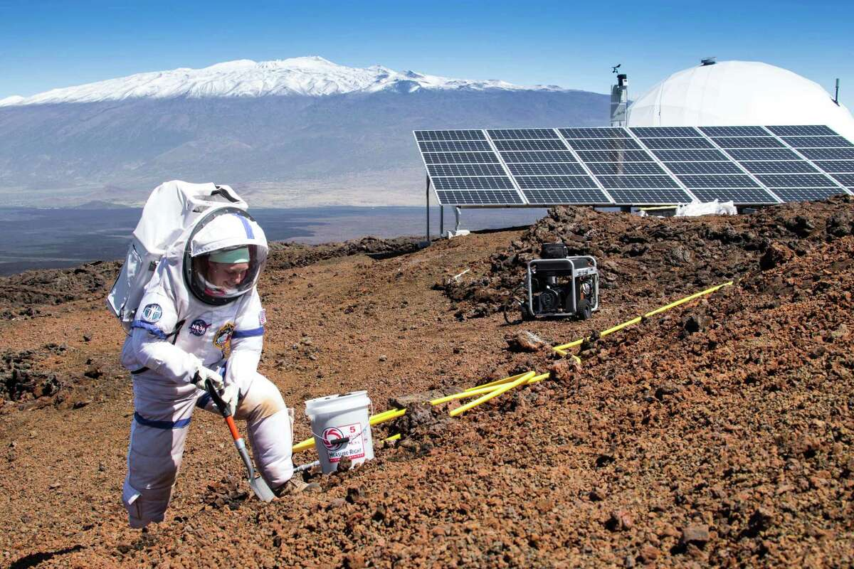 In this March 10, 2015, photo provided by the University of Hawaii at Manoa HI-SEAS Human Factors Performance Study, mission commander Martha Lenio collects a soil sample outside of the dome in which six scientists lived an isolated existence to simulate life on a mission to Mars, on the bleak slopes of dormant volcano Mauna Loa near Hilo on the Big Island of Hawaii. (Neil Scheibelhut/University of Hawaii at Manoa via AP)