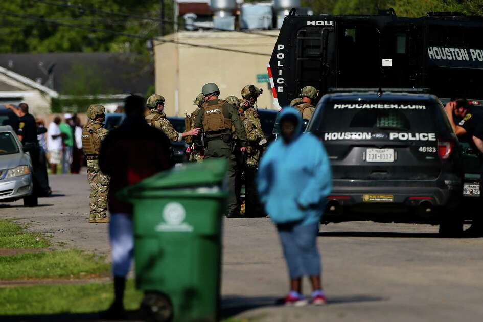 Houston Police SWAT officers respond to the scene of a standoff on the 4000 block of Grassmere Street Tuesday, March 26, 2019, in Houston. A man is holding hostage multiple people, including a one-year-old child, according to police.