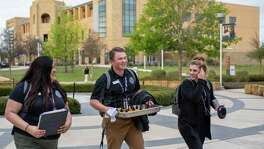 From left, Student Government Association members Emily Marquise, Clayton Jaskinia, and Marissa Lyssy walk through campus after a Student Government Association meeting at Texas A&M University San Antonio on Monday, March 18, 2019.