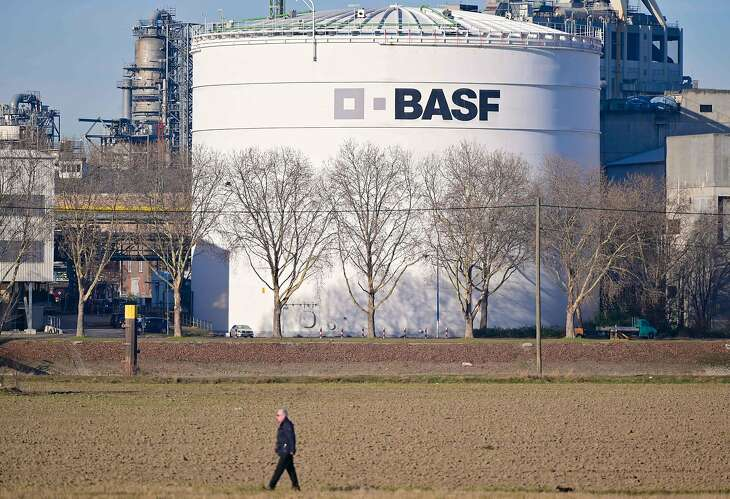 A man walks past tanks of German chemicals giant BASF at the company's headquarters in Ludwigshafen, western Germany, on February 26, 2019. - BASF reported its annual profits slumped in 2018, with knock-on effects from major customer sectors and geopolitical headwinds including trade conflicts taking the business off the boil. (Photo by Uwe Anspach / dpa / AFP) / Germany OUTUWE ANSPACH/AFP/Getty Images