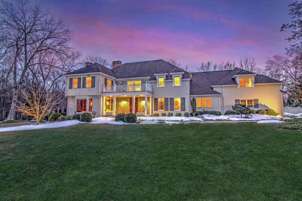 The Energy Star-rated white colonial house at 2 Arrowhead Way in Lower Weston sits on an attractively landscaped level property of 3.59 acres near the end of a cul-de-sac.