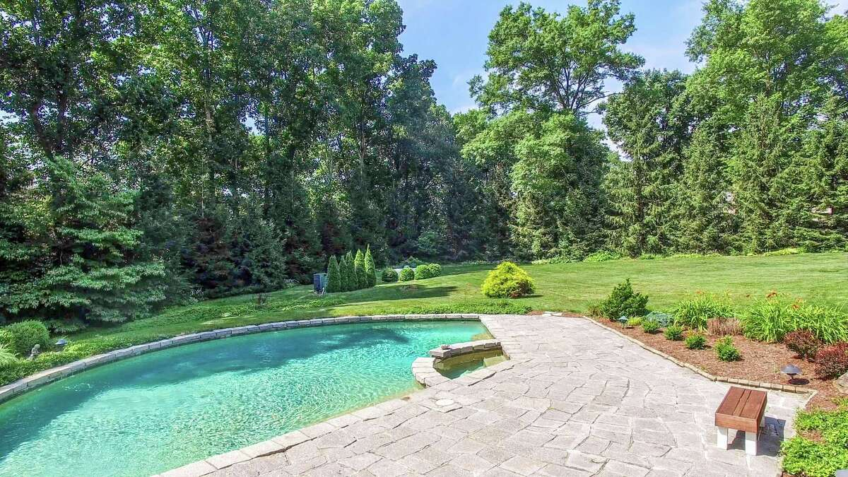 The nearly four-acre property features a semi-circular Gunite in-ground swimming pool and spa.