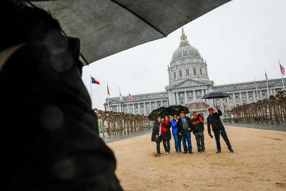 The Argentine family takes a family photo in the rain outside City Hall in San Francisco , California, on Monday, March 25, 2019.