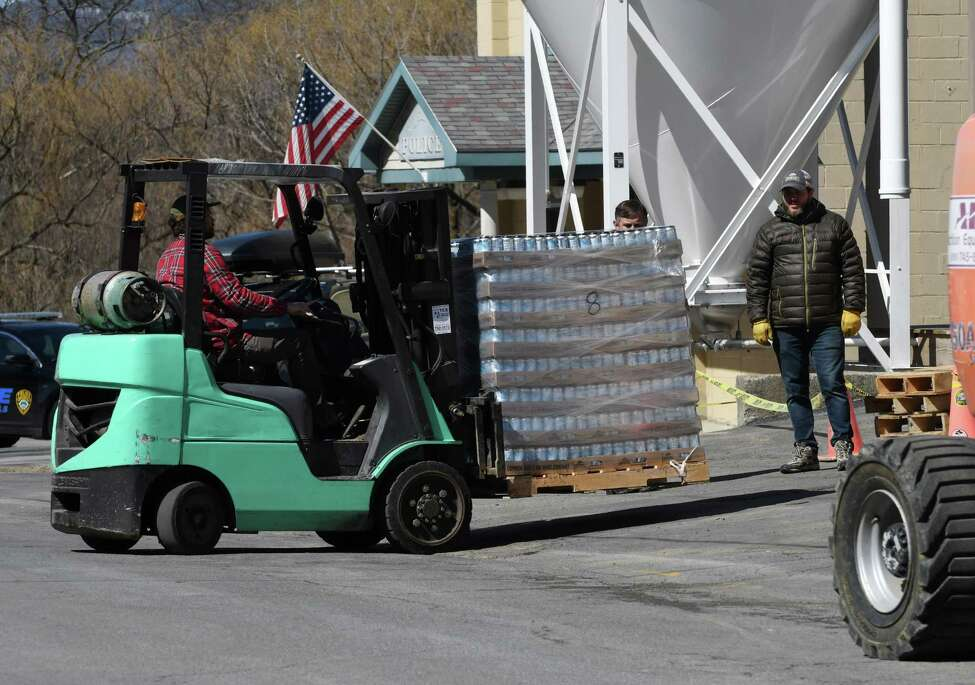 Cases of beer are taken out of the Commons Roots Brewing Company following a fire on Tuesday, March 26, 2019, on Saratoga Avenue in South Glens Falls, N.Y. The fire started on Monday night. (Will Waldron/Times Union)