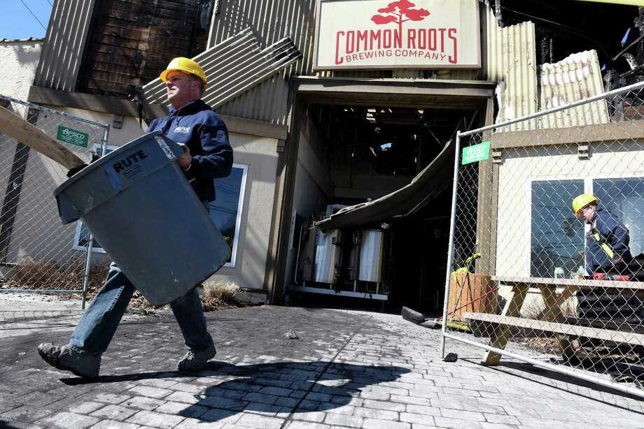 Workers remove debris form the Commons Roots Brewing Company following a fire on Tuesday, March 26, 2019, on Saratoga Avenue in South Glens Falls, N.Y. The fire started on Monday night. (Will Waldron/Times Union) Photo: Will Waldron, Albany Times Union