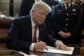 FILE - In this March 15, 2019, file photo, President Donald Trump signs the first veto of his presidency in the Oval Office of the White House in Washington. Trump issued the first veto, overruling Congress to protect his emergency declaration for border wall funding. Trump is nearing a victory over Democrats as the House tries overriding his first veto. Tuesday's vote seems certain to fail, which means his declaration of a national emergency at the Mexican border would stand. (AP Photo/Evan Vucci, File)