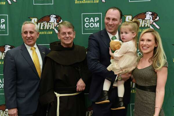 From left, Siena's Director of Athletics John D'Argenio, Br. F. Edward Coughlin, Carmen Maciariello and his daughter Reese, 2, and wife Laura pose for photos after Carmen was introduced as Siena's new head coach for their basketball team at the Times Union Center atrium on Tuesday, March 26, 2019 in Albany, N.Y. (Lori Van Buren/Times Union)