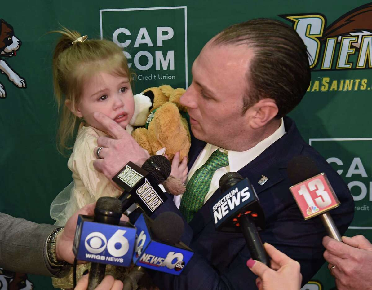 Carmen Maciariello wipes a tear from his 2-yr-old daughter Reese while speaking to the press after being introduced as Siena's new head coach for their basketball team at the Times Union Center atrium on Tuesday, March 26, 2019 in Albany, N.Y. (Lori Van Buren/Times Union)