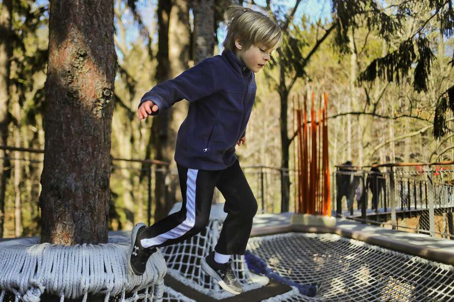 Kelton Kyro of Midland, 9, jumps onto a large cargo net at the Whiting Forest Canopy Walk on Tuesday, March 26, 2019 in Midland. (Katy Kildee/kkildee@mdn.net) Photo: (Katy Kildee/kkildee@mdn.net)