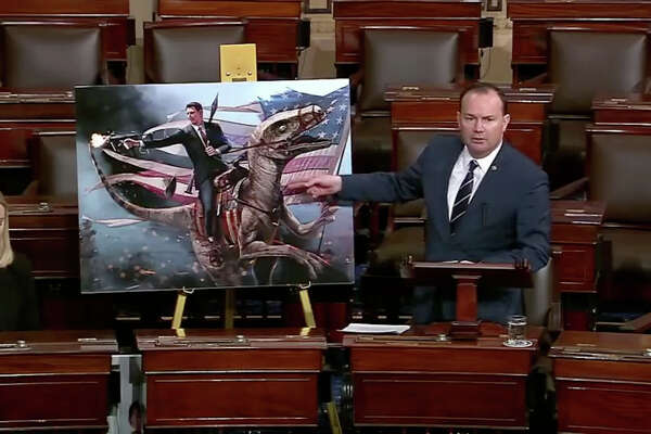 Rep. Mike Lee (R-Utah) uses an illustration of former President Ronald Regan riding a dinosaur while firing a gun to illustrate his critics of the Green New Deal in the U.S. House of Representatives on Tuesday, March 26, 2019.