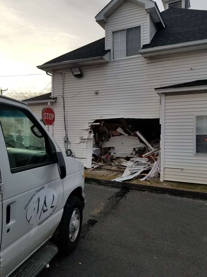 A van hit a building at 39 New St. in Danbury the evening of March 24, 2019, according to the Danbury Fire Department. The accident caused severe damage to the building — a house owned by the Philadelphia Pentecostal Church, and used as a rectory. The van's driver was uninjured. Photo: Danbury Fire Department / Contributed