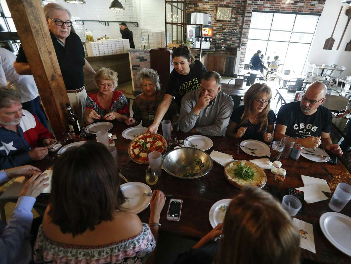 Nicole Bean, owner of Pizaro's, puts a pizza on the table during an Italian-themed food tour led by author Paul Galvani and Food Tours of Houston owner/operator Will Springfield, Saturday, March 23, 2019, in Houston.
