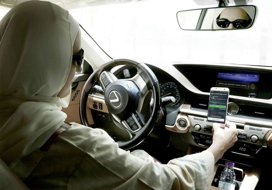 Ammal Farahat, a driver for Careem, opens the app on her mobile phone. Uber will continue to operate its own app in the Middle East, and Careem will become a wholly owned subsidiary. Photo: Nariman El-Mofty / Associated Press 2018