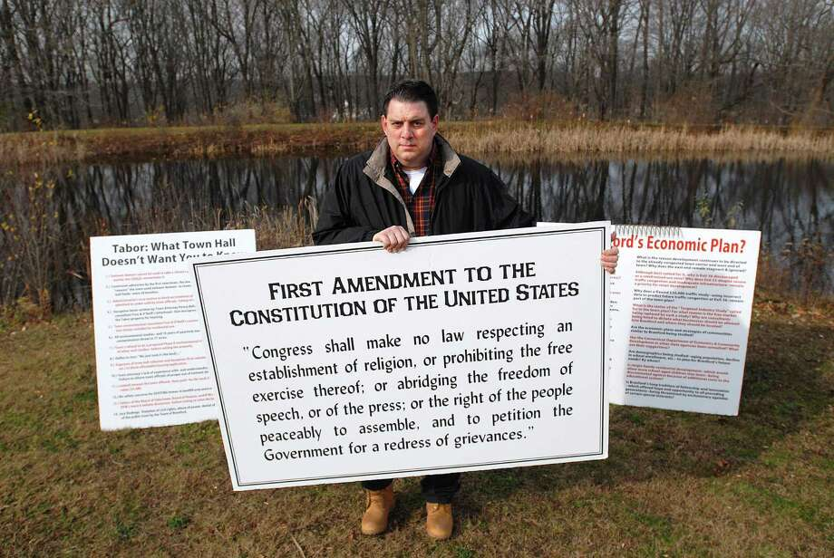 Wayne Cooke, owner of Hilltop Orchards in Branford, shows off some of the signs he brings to town meetings in this 2009 file photo. Photo: Hearst Connecticut Media File