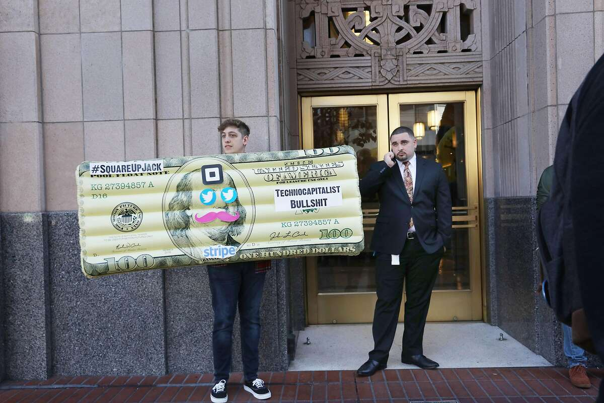 A tech worker who holds an inflated dollar bill with signs stuck on it stands in front of Twitter headquarters while attending aYes on C rally on Thursday, October 25, 2018 in San Francisco, Calif.