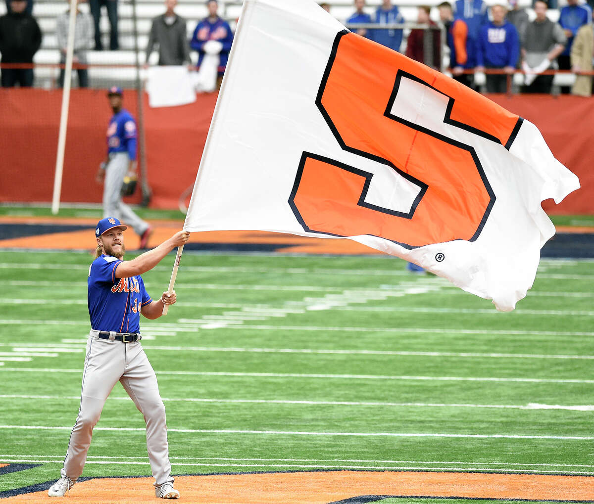 New York Met pitcher Noah Syndergaard waves the Syracuse University Flag at the fifty yard line. The Mets worked out at the Carrier Dome in Syracuse, N.Y., Tuesday, March 26, 2019. (Dennis Nett/The Post-Standard via AP)