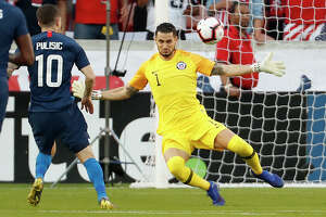 United States midfielder Christian Pulisic (10) kicks the ball over Chile goalkeeper Gabriel Arias (1) for a goal during the first half of an international friendly soccer match at BBVA Compass Stadium on Tuesday, March 26, 2019, in Houston.