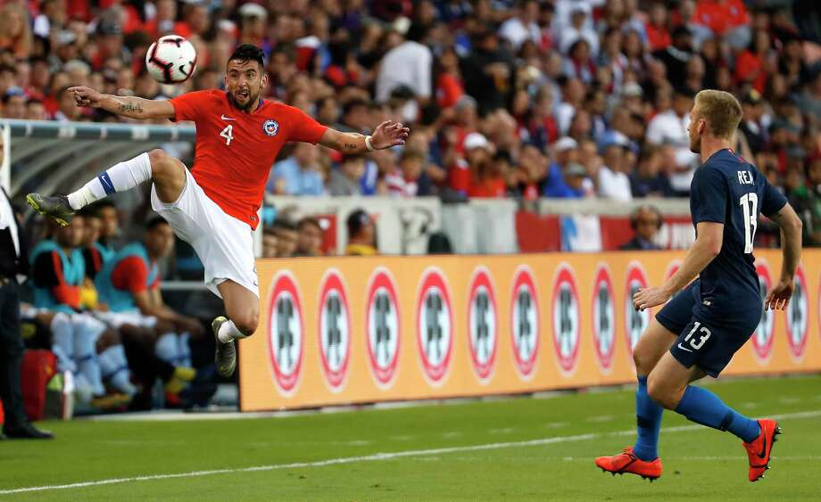 Chile defender Mauricio Isla (4) leaps for a wide ball headed for the sidelines against United States defender Tim Ream (13) during the first half of an international friendly soccer match at BBVA Compass Stadium on Tuesday, March 26, 2019, in Houston. Photo: Brett Coomer, Staff Photographer / © 2019 Houston Chronicle