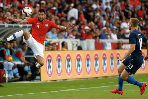 Chile defender Mauricio Isla (4) leaps for a wide ball headed for the sidelines against United States defender Tim Ream (13) during the first half of an international friendly soccer match at BBVA Compass Stadium on Tuesday, March 26, 2019, in Houston.