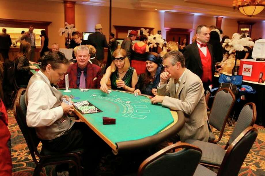 Attendees enjoy casino games and auction items during the third annual Feathers and Fedoras fundraiser for Disability Network of Mid-Michigan. (Photo provided/DNMM) 				  / copyright2016MARKI