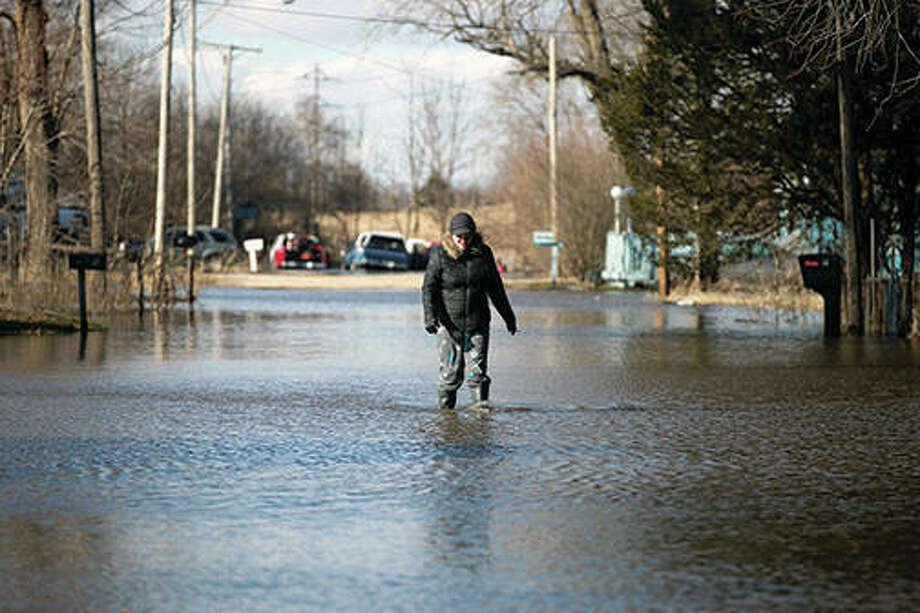 Allyson Hartman walks down flooded Louis Lane from her home in Freeport. Rising waters along the Pecatonica and Rock rivers have flooded homes in northern Illinois. Photo: Scott P. Yates | Rockford Register Star (AP)
