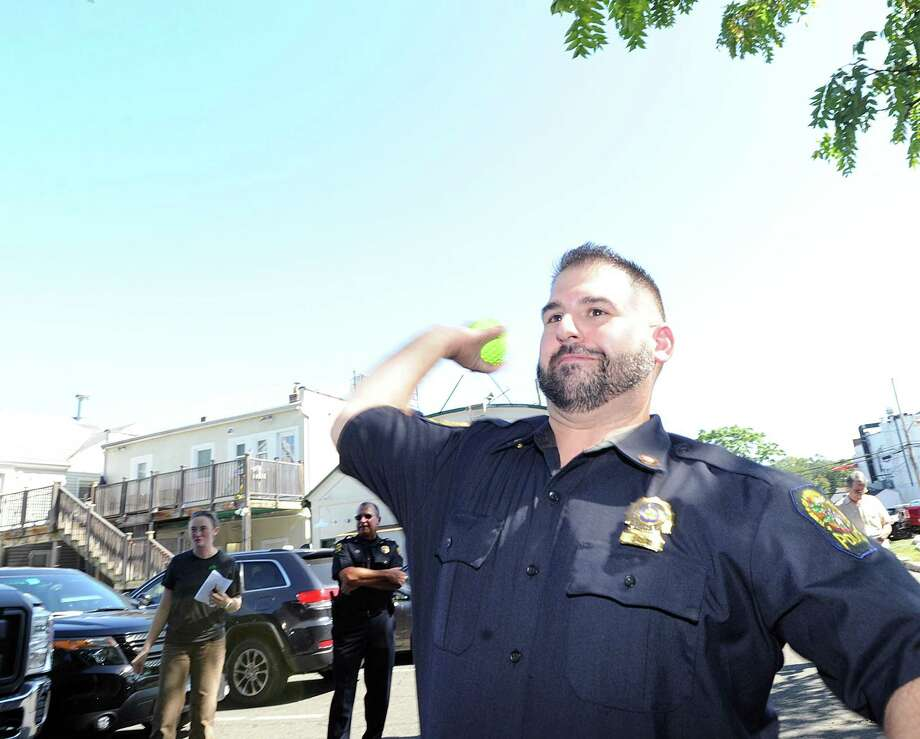 "Officer Dan Paladino tosses a ball toward a water-tank contraption during law enforcement appreciation day event in 2017. He will be one of the speakers Thursday as the Cos Cob Library hosts an event on ""Crime Prevention and Elderly Scams."" Paladino and other members of the Greenwich Police Department's Community Impact Section will speak from 2 to 3 p.m. in the Community Room. Sgt. Thorme will also attend with Detective Solomon and Officer Hirsch. Photo: File / Hearst Connecticut Media / Greenwich Time"