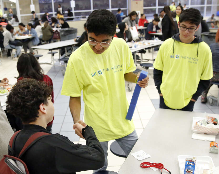 Duncanville High School freshman David Mojica, center, greets senior Paul Zamora, who was going to sign up to be a bone marrow donor, during lunchtime in the high school cafeteria, on March 21. The bone marrow drive was for Mojica, who suffers from aplastic anemia, a rare and life-threatening blood disorder. Photo: Tom Fox/The Dallas Morning News/TNS