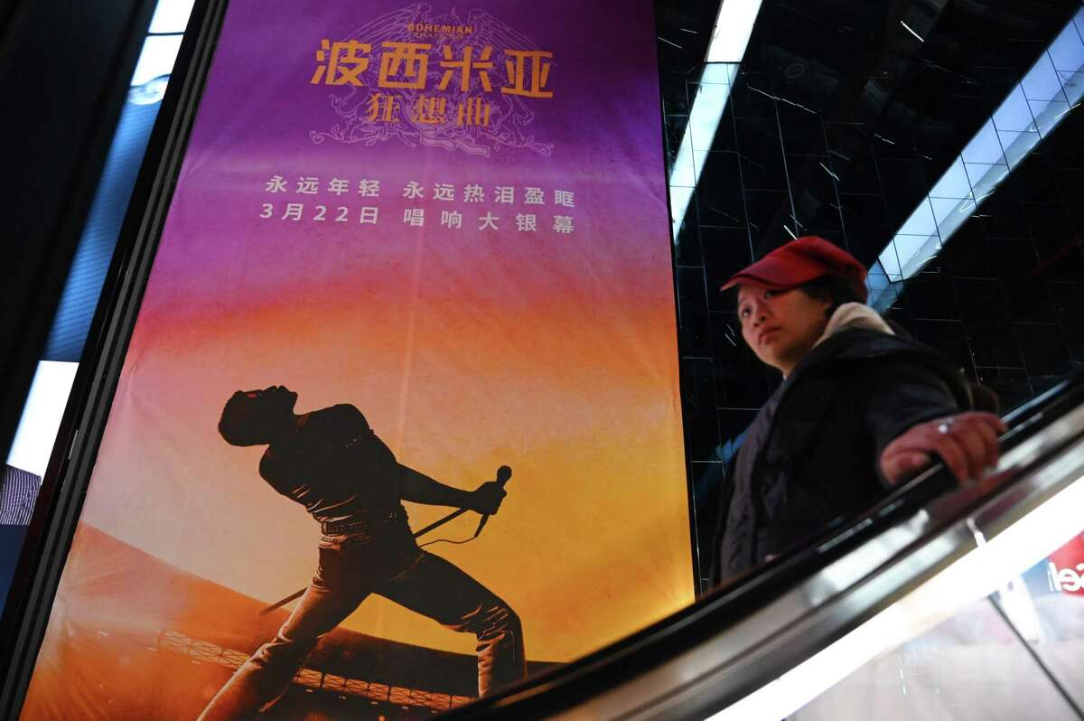 A woman rides an escalator past a poster for the film Bohemian Rhapsody at a movie theater in Beijing on March 27, 2019. - Scenes in the movie about rock band Queen have been censored in China to remove references about lead singer Freddie Mercury's sexuality. (Photo by GREG BAKER / AFP)GREG BAKER/AFP/Getty Images