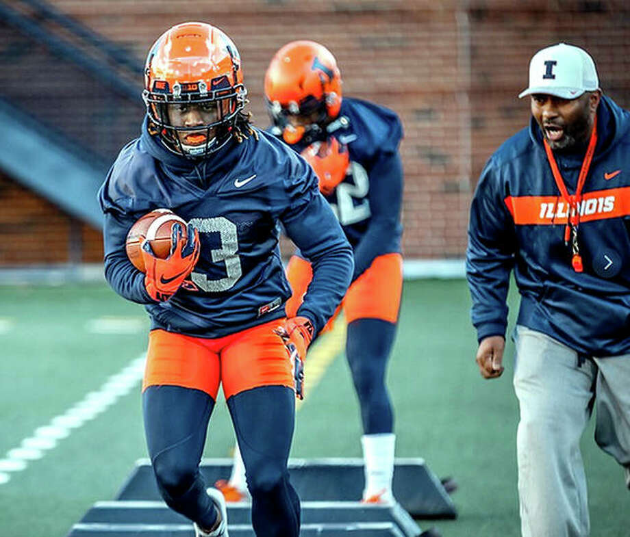 University of Illinois redshirt freshman running back Jakari Norwood (3) goes through a drill under the watchful eye of Illini running backs coach Mike Bellamy, right, during a spring football workout Tuesday at Memorial Stadium in Champaign. All workouts are closed to the public. The annual Orange and Blue Spring game will take place at 2 p.m. on Saturday, April 13, at 2 p.m. and will be free to the public. Photo: Fighting Illini Athletics