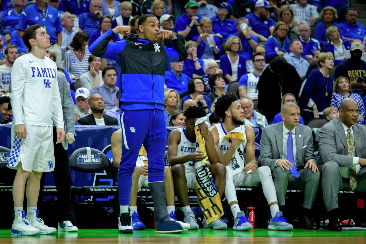 Kentucky forward PJ Washington, center, celebrates from the bench with a cast boot on his leg during the second half of the second round men's college basketball game against Wofford in the NCAA Tournament, in Jacksonville, Fla. Saturday, March 23, 2019. (AP Photo/Stephen B. Morton)
