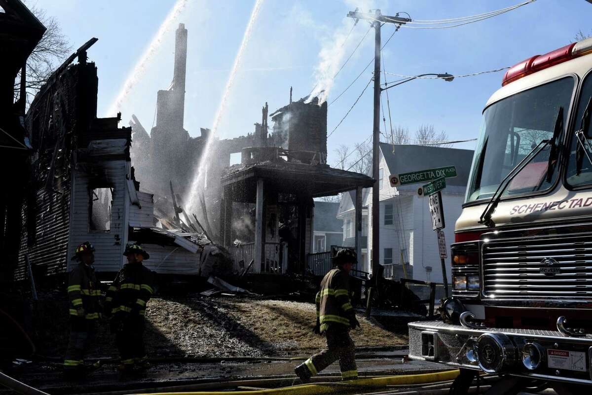Firefighters douse the remains of a Georgetta Dix Plaza home that was destroyed by fire on Wednesday morning, March 27, 2019, in Schenectady, N.Y. The flames spread to nearby house which sustained critical damage, leaving at least nine adults and children homeless in Hamilton Hill. (Will Waldron/Times Union)