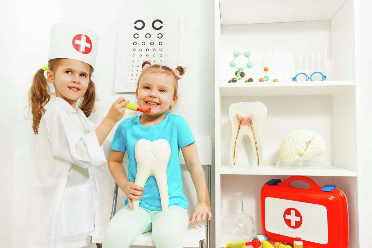 A young girl is dressed like a dentist, examines friend