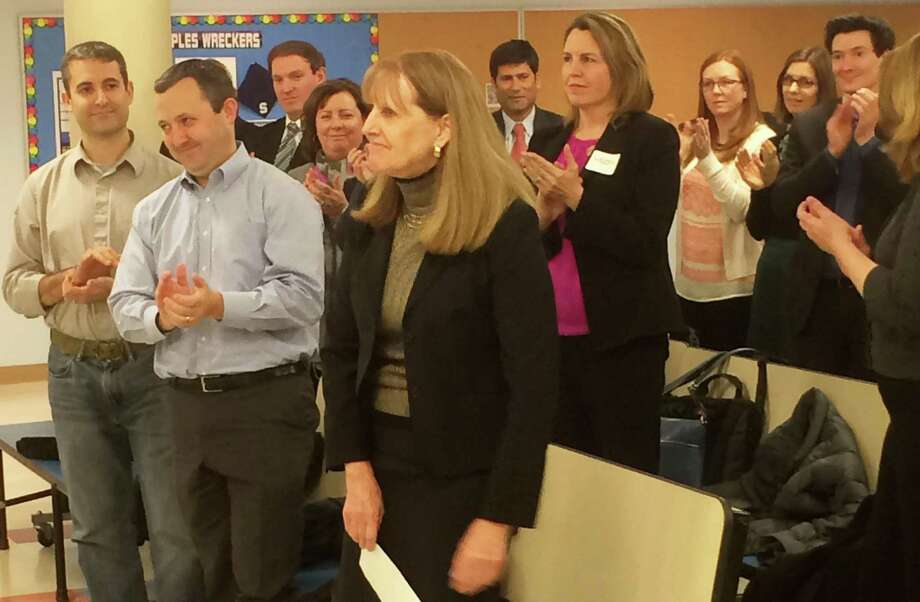 The audience at Monday's Board of Education meeting applauds Colleen Palmer, foreground, after the board officially named her the next superintendent of Westport's schools. Photo: Chris Marquette / Chris Marquette / Westport News