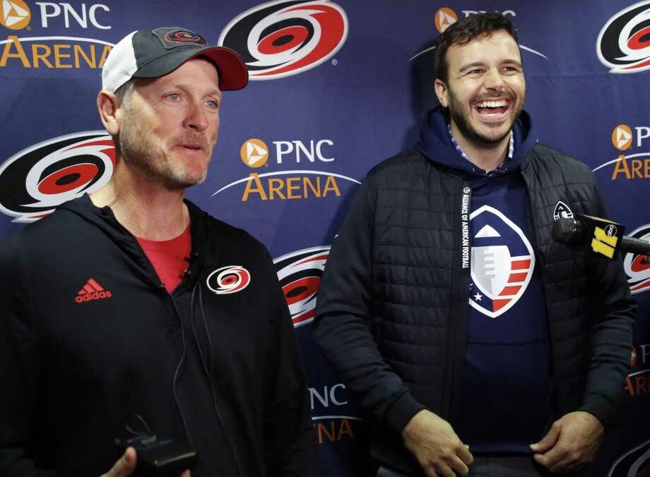 "FILE - In this Feb. 19, 2019, file photo, Tom Dundon, left, majority owner of the Carolina Hurricanes, and Charlie Ebersol, co-founder and CEO of the Alliance of American Football, talk to the media about Dundon's $250 million investment in the league, before an NHL hockey game between the New York Rangers and the Hurricanes in Raleigh, N.C. It's too early to tell what impact the Alliance of American Football will have on the sport itself. After all, this is its fourth weekend of games. Away from the field, with an infusion of backing from Dundon, the AAF is finding its footing. It's also finding what Ebersol calls ""substantial interest"" in the league in such areas as sponsorships and partnerships, with three new partners signing on since the season opener three weeks ago. (AP Photo/Chris Seward, File) Photo: Chris Seward, FRE / Associated Press / Copyright 2019 The Associated Press. All rights reserved"