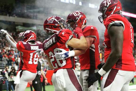Teammates help Kenneth Farrow II celebrate the first San Antonio touchdown as the Commanders host San Diego at the Alamodome in the opening game for the Alliance of American Football league on February 9, 2019.