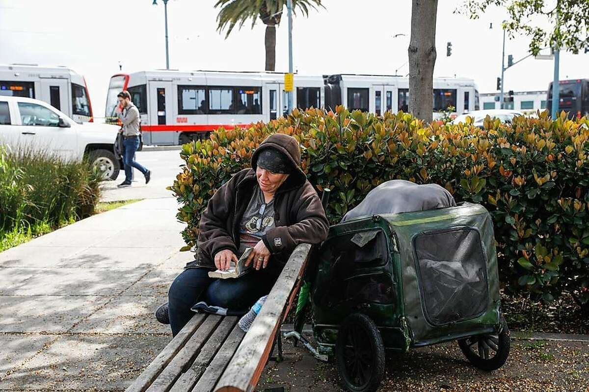 A homeless woman named Keri reads near a parking lot along the Embarcadero in San Francisco, California, on Wednesday, March 27, 2019. The parking lot has been proposed by Mayor London Breed as a potential Navigation Center.