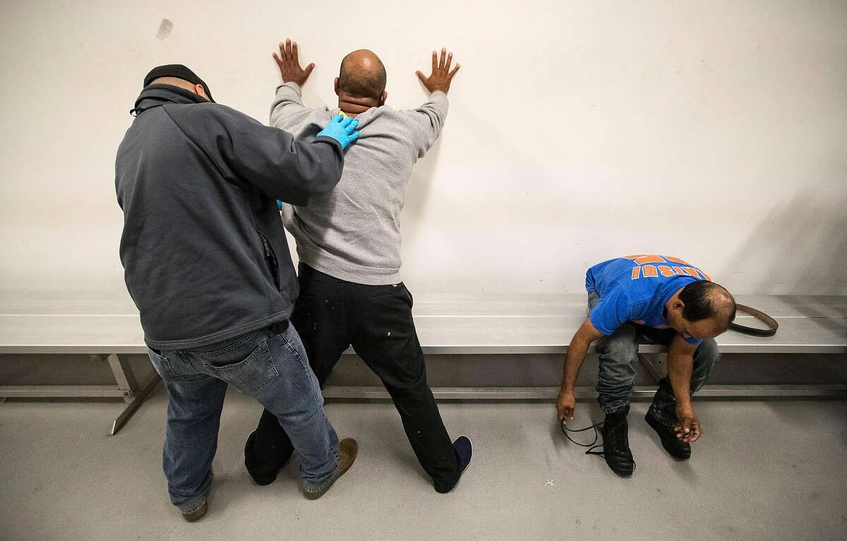 LOS ANGELES, CALIF. -- TUESDAY, APRIL 18, 2017: An Immigration and Customs Enforcement agent, left, searches Esteban Amigon, center, while green card holder Sergio Rodriguez removes his belt and shoelaces while they are processed the ICE downtown staging facility in Los Angeles, Calif., on April 18, 2017. (Brian van der Brug/Los Angeles Times via Getty Images)