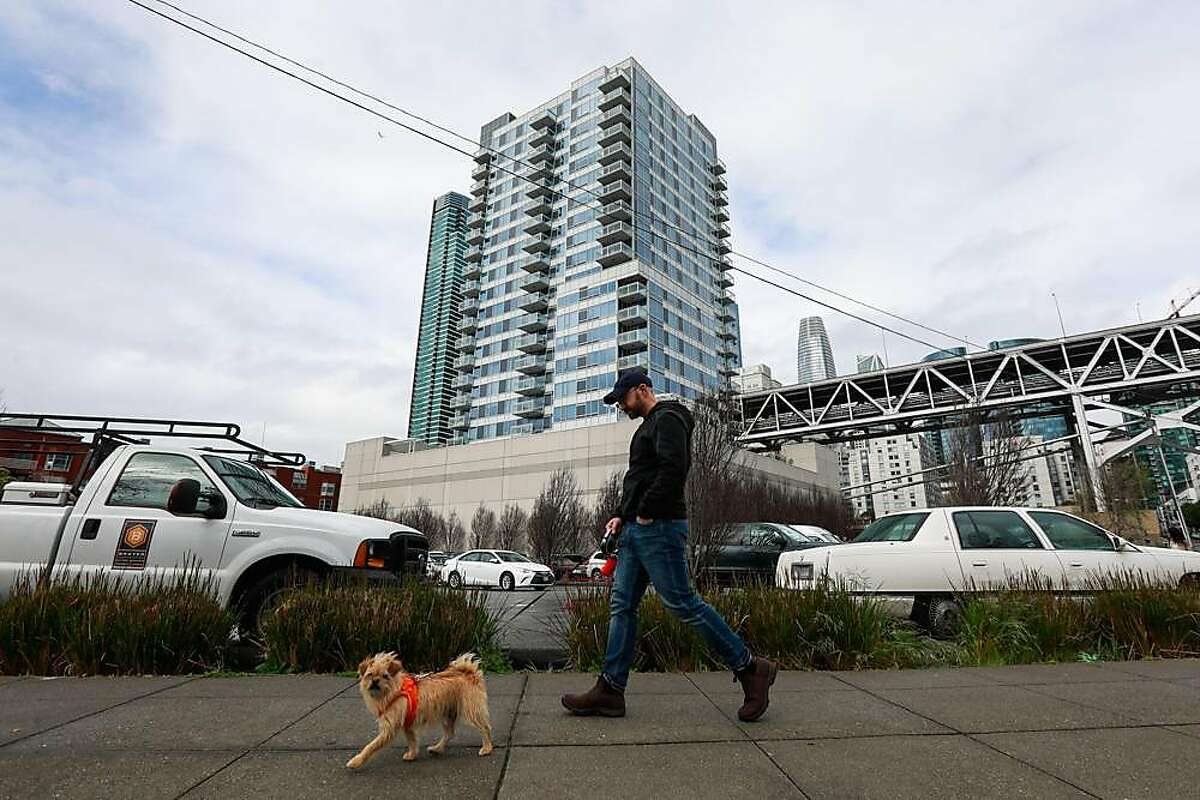 Kelvin Lynch walks his dog Oliver as he passes by the Watermark apartment complex which is situated next to a parking lot that is being proposed by Mayor London Breed to become a Navigation Center in San Francisco, California, on Wednesday, March 27, 2019.