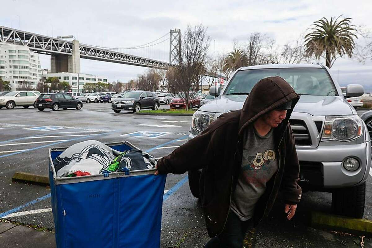 A homeless woman named Keri walks her belongings out of a parking lot that is situated next to the Watermark apartment complex in San Francisco, California, on Wednesday, March 27, 2019. The parking lot has been proposed by Mayor London Breed as a potential Navigation Center.