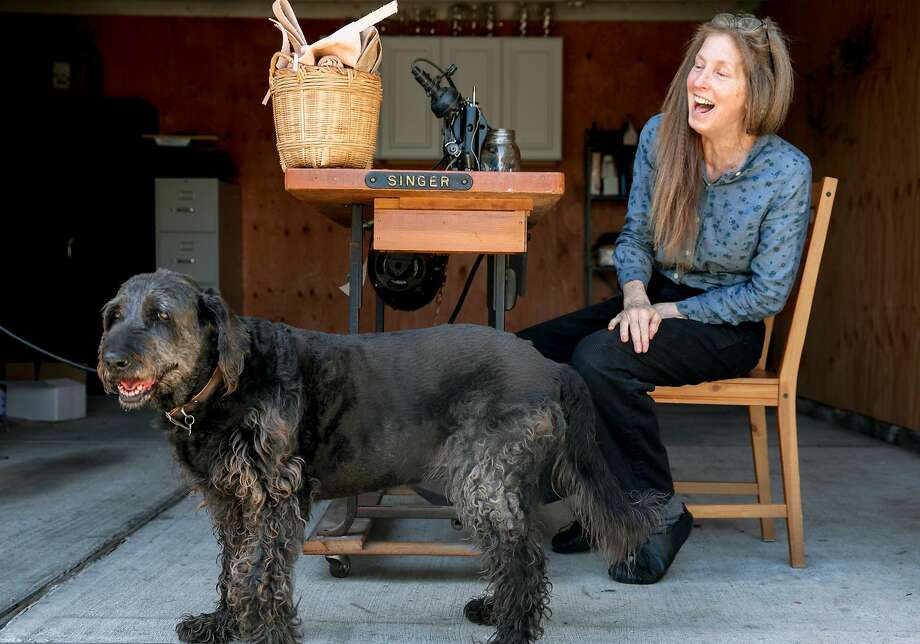 Lori Stone works at a sewing machine at her Redwood City home alongside her dog, Reese. Photo: Jessica Christian / The Chronicle