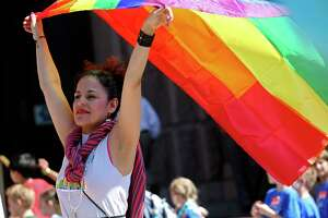 Erika Flores Casasola, of San Antonio, raises the gay pride flag during a rally in front of the state Capitol building, Monday, March 20, 2017. Members and supporters of the LGBTQ community rallied and voiced their opposition to SB6. Known as the bathroom bill, it regulates the usage of the facilities by making transgender people use the bathroom based on their birth gender.