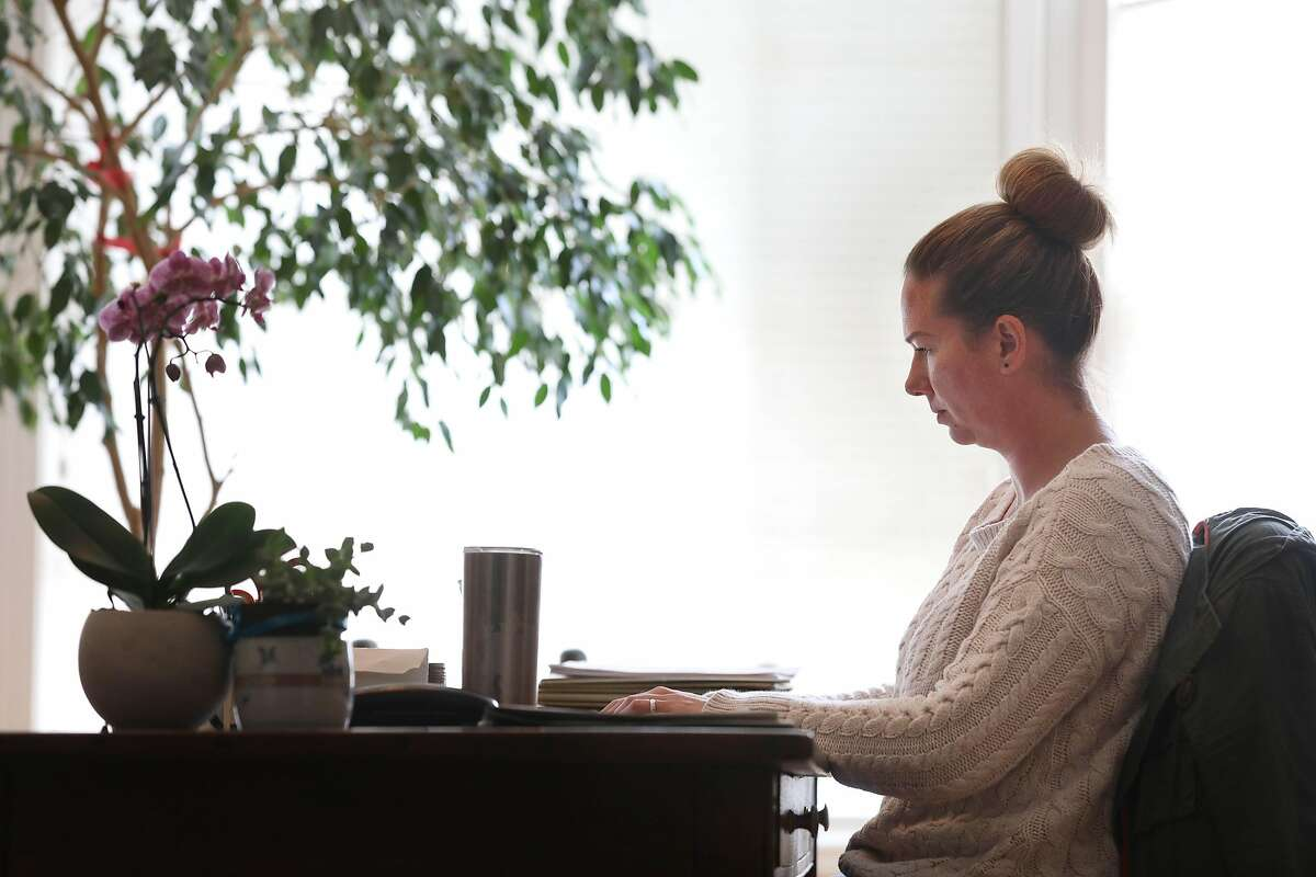 Rebecca Stack-Martinez , who drives for Lyft and Uber and works part-time as a research analyst , types on a laptop as she works as a research anaylst on Wednesday, March 27, 2019 in San Francisco, Calif.