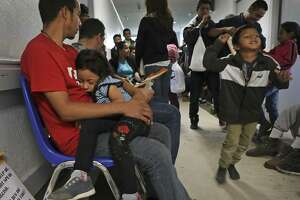 Nestor Sosa of Honduras cradles his sleeping 5-year-old daughter in a crowded hallway at the Catholic Charities Respite Center in McAllen on March 21, 2019. Customs and Border Protection officials are releasing thousands of migrant families because the agency said it doesn't have space to detain them all.