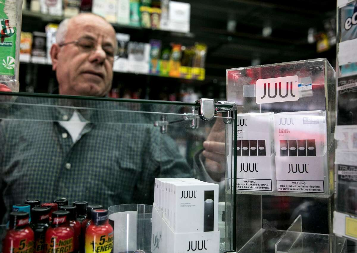 The Town Smoke Shop employee Walid Rahman shows a display case of Juul products in the Mission district of San Francisco, Calif. Thursday, March 21, 2019.