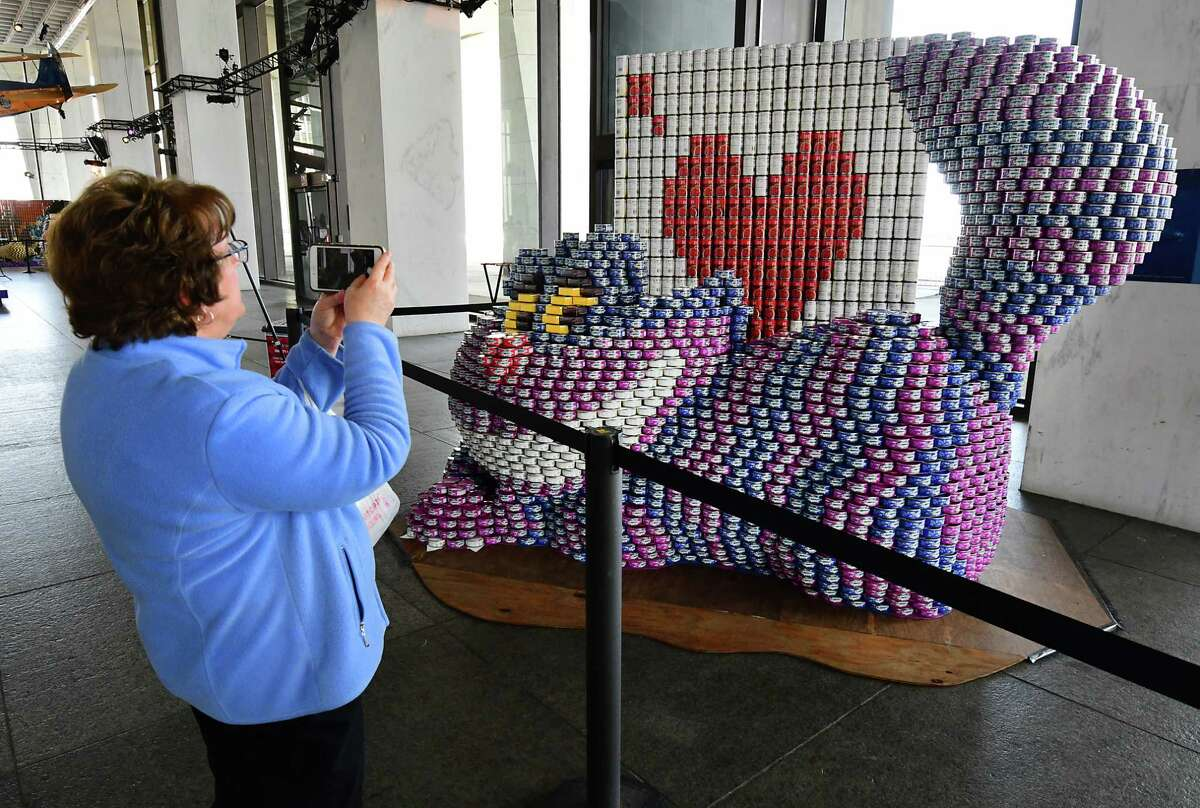 Linda Miller of Guilderland takes a photo of cans of tuna built in the shape of a Cheshire cat during this year?s Canstruction ?Disney? themed program at the New York State Museum on Wednesday, March 27, 2019 in Albany, N.Y. The program will be benefiting the Food Pantries for the Capital District. (Lori Van Buren/Times Union)