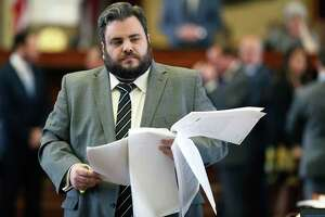 Rep. Jonathan Stickland, R-Bedford, walks the floor with pages of legislative material as the Texas House of Representatives takes up the budget bill on March 27, 2019. He is one of eight Republican House members who narrowly won his reelection in 2018, making him a prime target for Democrats.