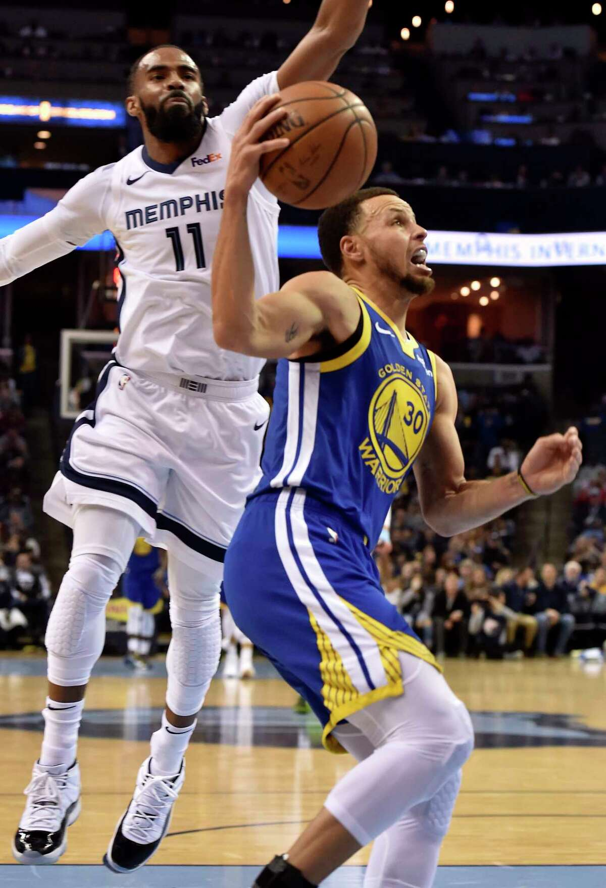 Golden State Warriors guard Stephen Curry (30) drives to the basket ahead of Memphis Grizzlies guard Mike Conley (11) in the second half of an NBA basketball game Wednesday, March 27, 2019, in Memphis, Tenn. (AP Photo/Brandon Dill)